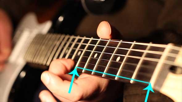 Guitar string vibrating behind hand